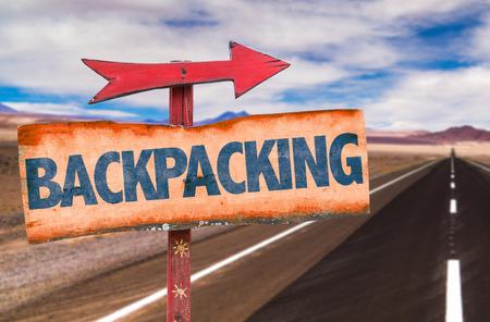 Foto de Backpacking sign with arrow on road background - Imagen libre de derechos