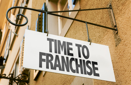Time to franchise signpost on building background