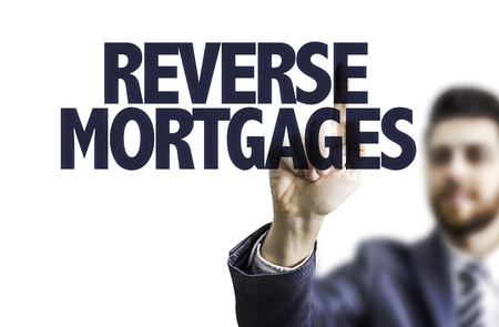 Photo pour Business man pointing to transparent board with text: Reverse mortgages - image libre de droit
