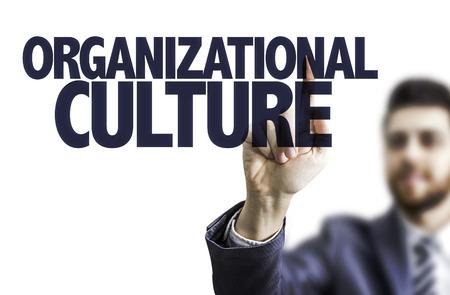 Photo pour Business man pointing to transparent board with text: Organizational culture - image libre de droit