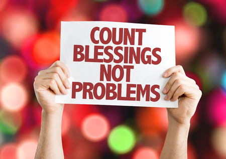 Hands holding cardboard on bokeh background with text: Count blessings not problems