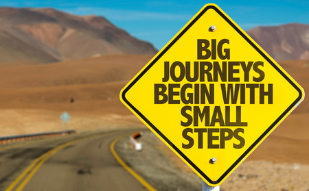 Photo for Big journeys begin with small steps sign on a highway background - Royalty Free Image