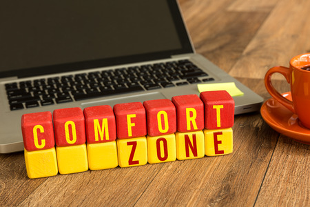Photo for Comfort zone written on a wooden cube with laptop background - Royalty Free Image