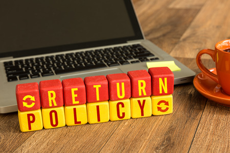 Return policy written on a wooden cube with laptop background