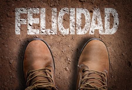 Text on road with boots background: Felicidad (happiness in Spanish)