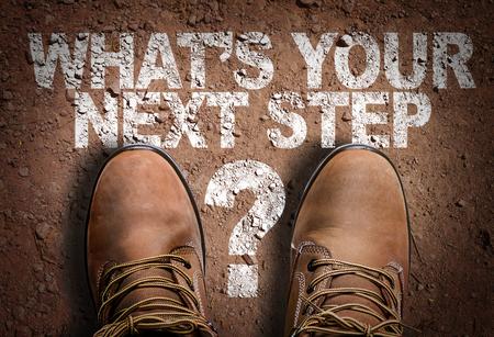 Foto de Text on road with boots background: What's your next step? - Imagen libre de derechos