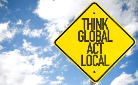 Think global act local sign with clouds and sky background