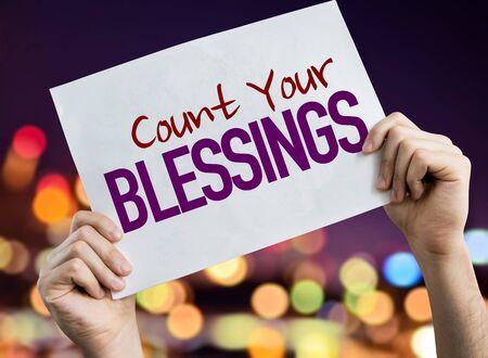 Photo pour Hands holding Count Your Blessings placard with bokeh background - image libre de droit