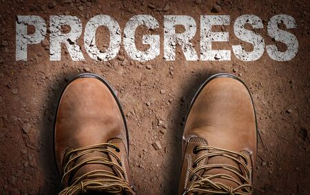 Photo pour Boots on the trail with the word Progress - image libre de droit