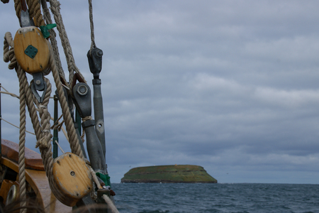 Ropes of an ancient whaler in the foreground and in the background the island where the puffins live