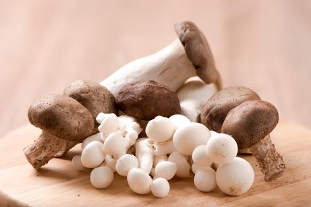 King oyster mushroom and shimeji mushroom and Shitake mushroom on chopping block ,wood table