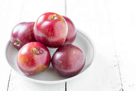 big ripe plums in a ceramic saucer on white boards closeup