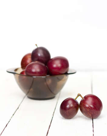 big ripe plums in glass wares on white boards