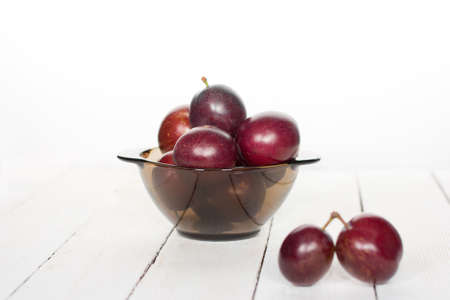 big ripe plums in glass wares on a white background
