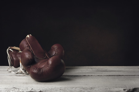 Boxing Gloves lying on two wooden Planks