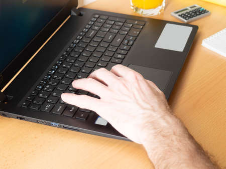 Foto de Laptop, mans hands, home furnishings, juice, books. The concept of working online, learning online. - Imagen libre de derechos