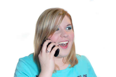 portrait of young teenage eighteen year old woman in casual clothing smiling and talking on a cellphone