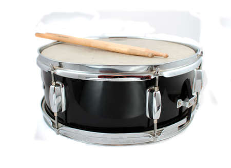 Snare drum and drumsticks on a white background (short depth of field)