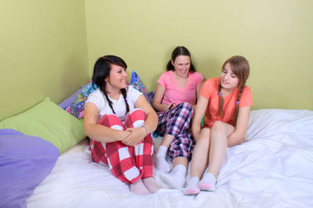Group of three teenage girls hanging out on a bed in their pyjamas ready for a sleepover or slumber party