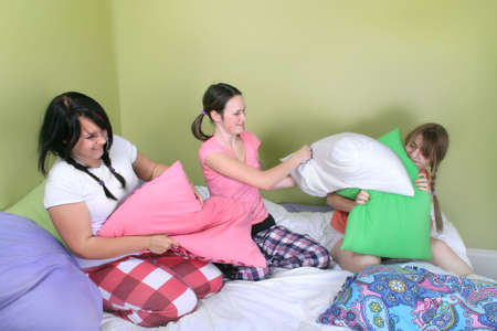 Three teenage girls in their pajamas with pigtails or braids having a pillow fight on a bed at a sleepover