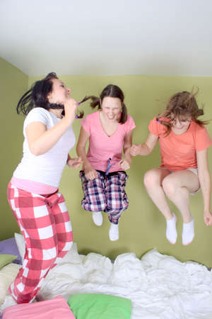 Teen girls having a sleepover jumping up and down on the bed (some motion blur)