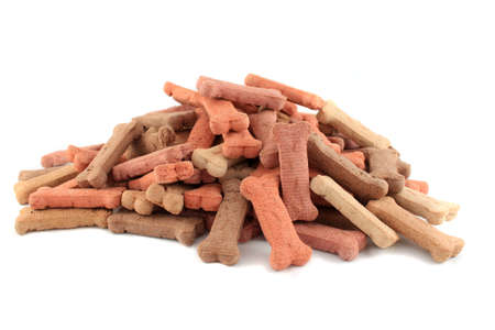 Pile of dog biscuits in the shape of a bone on a white background (not isolated)