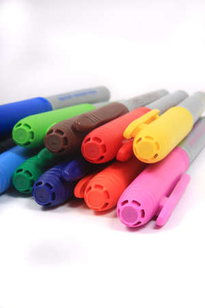 Colorful rainbow markers piled up  in blue, green, yellow and reds on a white background