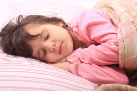 Cute little girl laying in bed sleeping cozy on her pillow and in her blanket