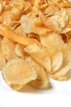 Closeup of kettle chips spilling over on a white background
