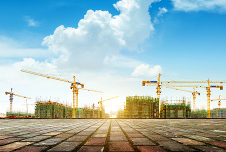 Photo pour Crane and building construction site against blue sky - image libre de droit