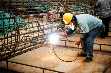 Photo for welder worker welding metal by electrode with bright electric arc and sparks during manufacture of metal equipment - Royalty Free Image
