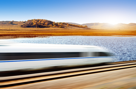Dynamically blurred train passing the grassland river