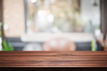 Foto de Empty wooden desk space and blurry background of restaurant vintage tone for product display montage - Imagen libre de derechos