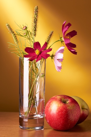 Still life with flowers and apples on yellow background