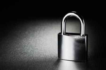 Photo pour Steel padlock on the black textured background - image libre de droit