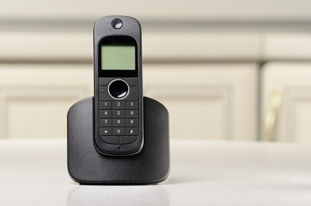 Black cordless phone standing on a table