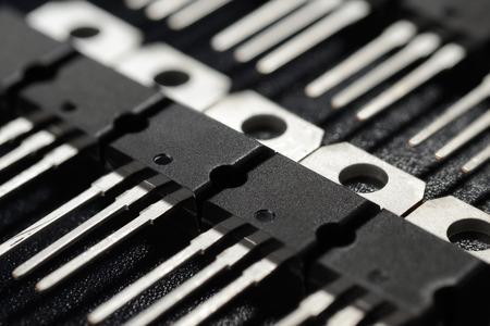 Macro shot of power transistors on the black surface
