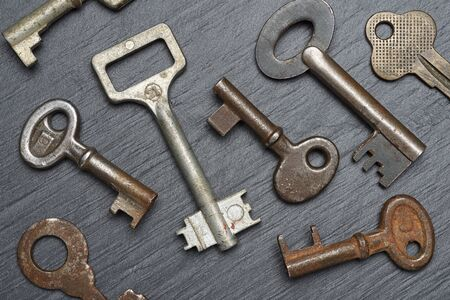 Photo for Heap of old rusty lever tumbler keys on black slate background - Royalty Free Image