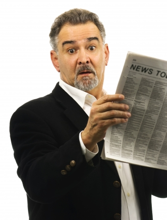 A mature man looks surprised; shocked; awestruck while reading a newspaper.
