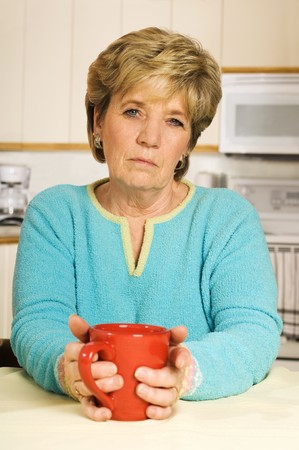 Senior woman holds a coffee mug, looking unhappy.