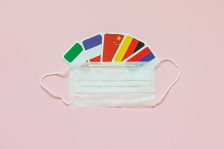 Flags of countries France, Italy, Russia, Germany, Protective medical mask on pink background. Country Coronavirus Disease Concept, COVID-2019, pandemic. Uniting countries against a pandemic
