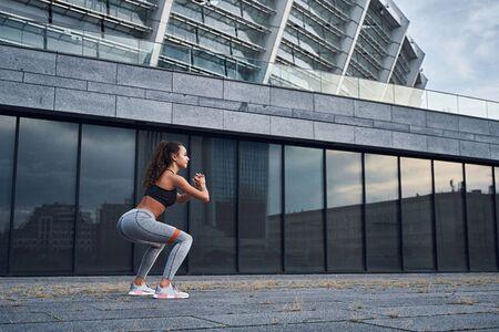 Foto de Young athletic woman doing squats exercises with sports rubber at the urban city location - Imagen libre de derechos