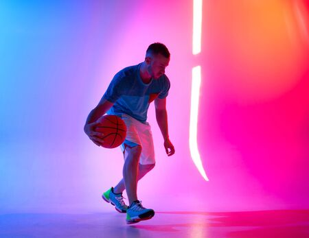 Photo pour Young athletic man dribbling with basketball ball posing on mix of blue and pink background with light projection - image libre de droit