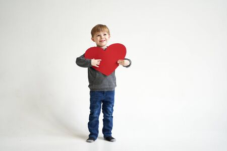 Photo pour Sweet boy holding red paper heart on white background. Valentines day or kids healthcare, medical concept - image libre de droit