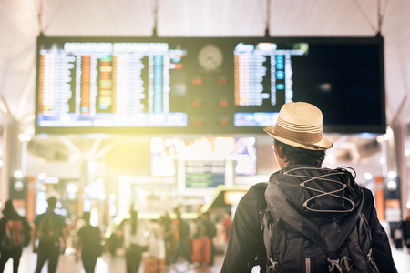 Foto de young traveler or tourist looking at airport time board for flight schedule, travel, holiday, tourism and holiday concept - Imagen libre de derechos