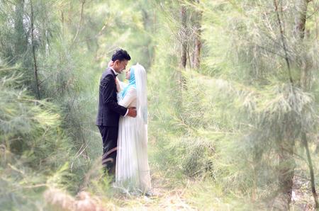 Foto de Outdoor portrait of a beatiful malay bride and groom couple in a garden. Concept of wedding and relationship - Imagen libre de derechos