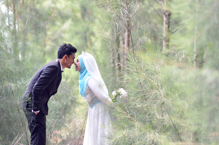 Foto de Outdoor portrait of a lovely malay wedding couple in a beautiful park. concept of love, relationship and wedding - Imagen libre de derechos