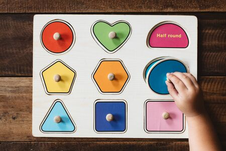 Photo pour Child matching a toy shape puzzle on wooden table. Concept of early education and child development - image libre de droit
