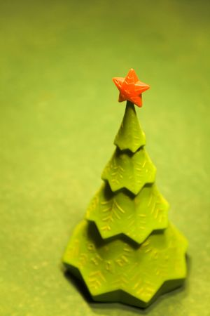 green christmas tree with a red star on top on a billiard table