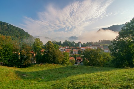 Scenic view of Most na Soci (Santa Lucia d'Isonzo) village, Slovenia at summer morning. Meadow, roofs of small houses and tall church bell tower with mountains on background under picturesque sky